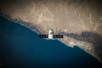 Space Satellite hovering above the coast; Source